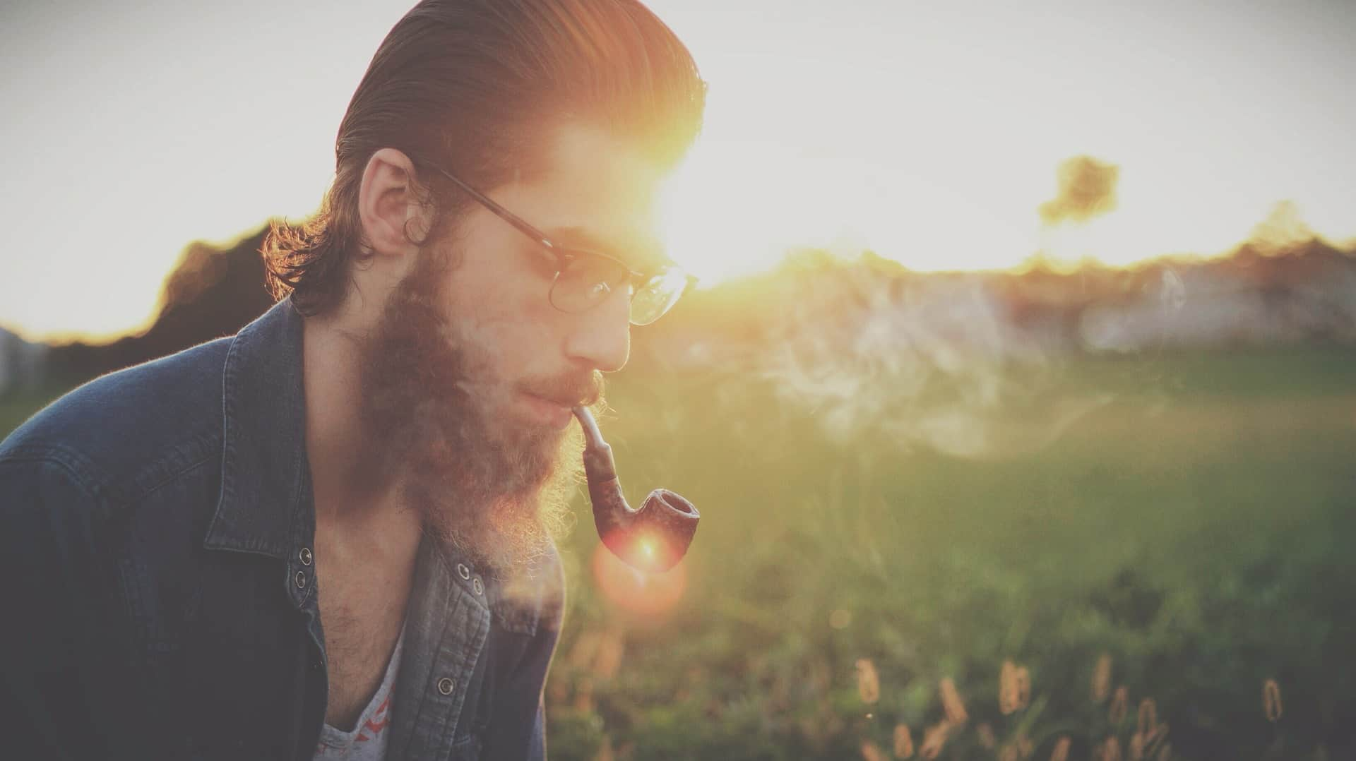 Man wearing glasses and smoking a pipe